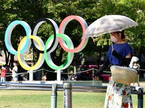 五輪マークのモニュメント近くで日傘を差して歩く人=7月31日、札幌市