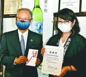 蔵元の松浦さん(右)から寄付を受け取った熊谷理事長=鳴門市大麻町の本家松浦酒造場