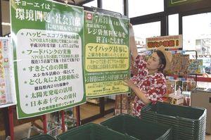 8月からのレジ袋有料化を知らせるポスターを掲示する従業員=徳島市南田宮2のキョーエイ三ツ合橋店