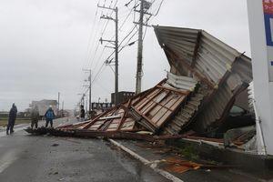 空き店舗の一部が屋根ごと飛ばされ、大型量販店のフェンスを押しつぶした=4日午後、阿南市日開野町
