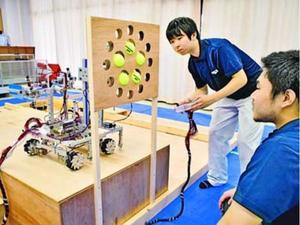 自作した操縦型ロボットでテニスボールを穴に入れる藍科技のメンバー=徳島市の徳島科学技術高校