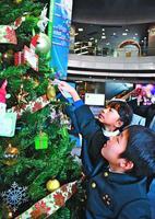 クリスマスツリーにメッセージカードを付ける児童=北島町の県立防災センター