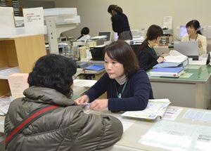 個人番号カードを町民に交付する町職員=午前9時半ごろ、松茂町総合会館