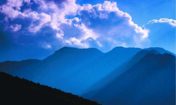 三嶺と湧き上がる雲。光が射し込み水墨画のような光景を作り出す=三好市東祖谷山菅生