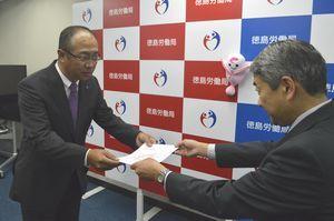 飯野局長から「プラチナくるみん」の認定通知書を受け取る松本社長(左)=徳島市の徳島労働局