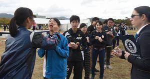 なると金時の大学いも「芋棒」を食べさせるリレーに挑む参加者=鳴門ウチノ海総合公園