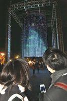 スマホを使ってクリスマスツリーの映像に飾り付けをする来場者=藍場浜公園