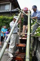 住民の手ほどきを受けて足踏み水車を体験する子ども=佐那河内村役場前