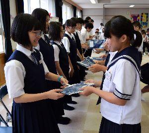 音別中生(左側)に手作りの藍染のバンダナを贈る鷲敷中生=鷲敷中