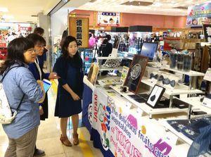 藍染製品を手掛ける県内業者(右)から説明を受ける来場者=台湾台北市太平洋そごう忠孝館(県提供)