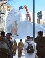 「さっぽろ雪まつり」が閉幕し、大雪像の解体作業の様子を見る人たち=12日午前、札幌市中央区