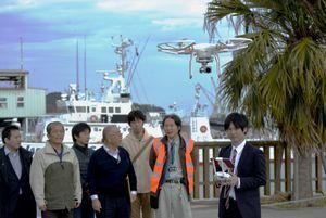 ドローンを操縦する茨木さん(右端)=小松島市小松島町のみなとオアシス交流広場