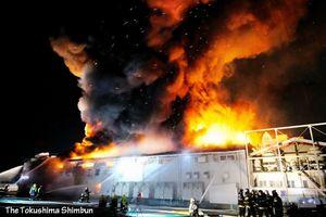 炎と黒煙を上げながら燃える工場=16日午後6時42分、松茂町満穂