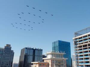 「100」の形の編隊で北京市上空を飛ぶヘリコプター=19日(共同)