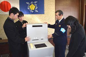 寸劇用ATMの組み立て方を美馬署員に教えるつるぎ高生(左の2人)=同署