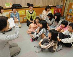 子どもたちに絵本を読み聞かせるにじの会の会員=藍住町立図書館