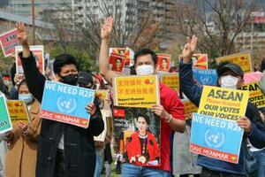 ミャンマー国軍によるクーデターに抗議し、3本指を突き出す人たち=7日午後、神戸市