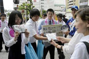 堆肥やアサガオの種を配り、地球温暖化防止を訴える高校生=徳島駅前