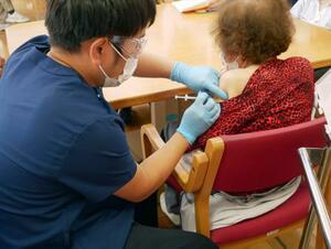 「銀杏の丘デイサービスセンター」で、利用者(右)に新型コロナウイルスワクチンを接種する看護師=21日午後、群馬県伊勢崎市