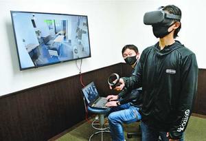ゴーグルを着けて仮想現実内のモデルハウスを内覧する担当者=徳島市のMCS