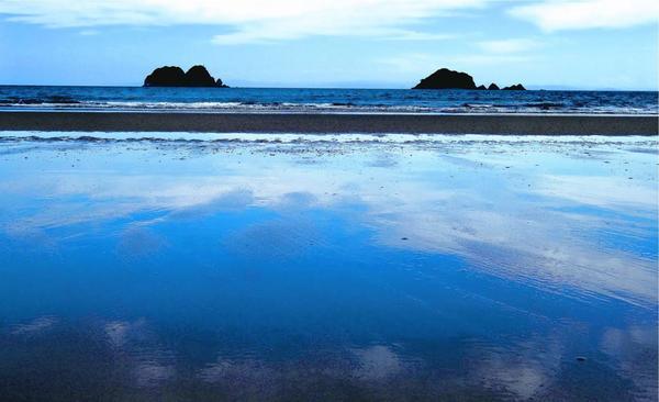 大潮の淡島海岸は、潮が引いた砂浜に空が映り込む絶景が広がる=阿南市畭町