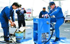 足こぎ式の給油装置で地下タンクからガソリンをくみ上げる参加者=小松島市大林町の髙木石油