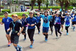 思い思いに藍色の服やパンツを着てゴールインする参加者=徳島市の藍場浜公園