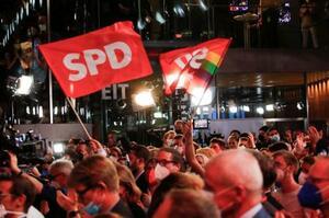 SPDの党本部で、ドイツ連邦議会選の得票予測を受け旗を振る支持者ら=26日、ベルリン(ロイター=共同)