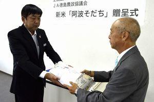 片山園長(右)に新米を手渡すJA全農とくしまの大西本部長=徳島市の県JA会館