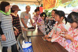 夏祭りで子どもにタコ焼きを振る舞う吉田会長(左から3番目)ら地域住民=阿波市阿波町岩津の八幡神社