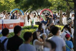 7月31日、国立競技場近くの五輪マークのモニュメント周辺で、記念撮影待ちの列をつくる人たち=東京都新宿区
