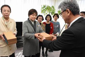 竹中所長(右端)に図書を贈る会員=徳島市入田町の徳島刑務所