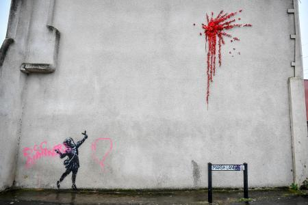 英南西部ブリストルで見つかった後、ピンク色のスプレーで落書きされたバンクシー作品(英PA通信=共同)