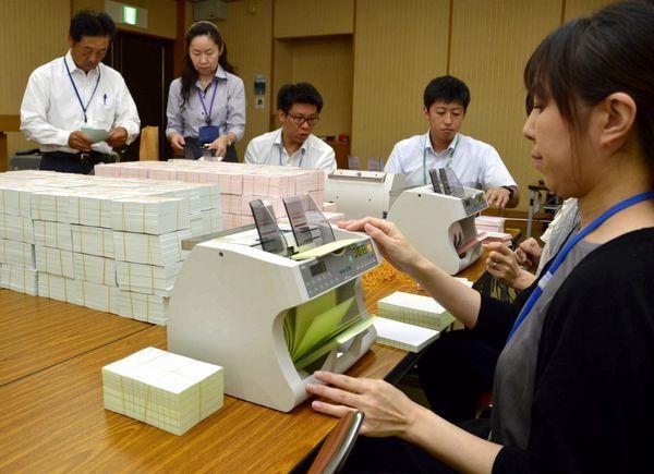 計数器で衆院選の投票用紙の枚数を確認する市町村選管の担当者=県庁
