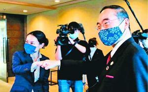 飯泉知事(右)に出迎えられ、握手の代わりにグータッチする内藤市長=県庁