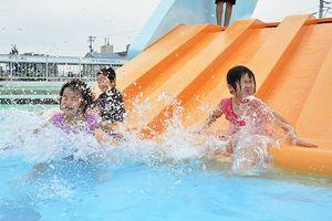 幼児用プールのスライダーを楽しむ子ども=徳島市のワークスタッフ田宮プール