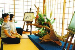四宮さんの書と陣原さんの生け花がコラボした作品に見入る来館者=徳島市の徳島城博物館