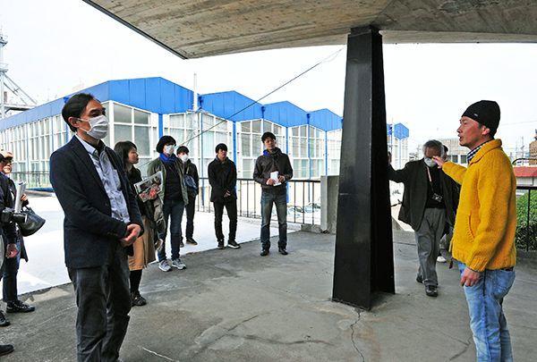 鳴門市役所の玄関前で見学会の参加者に建物の概要を説明する建築家の福田頼人㊨=3月18日