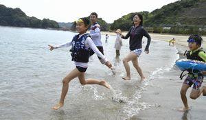 砂浜から海に駆け出していく家族連れ=海陽町浅川の大砂海水浴場