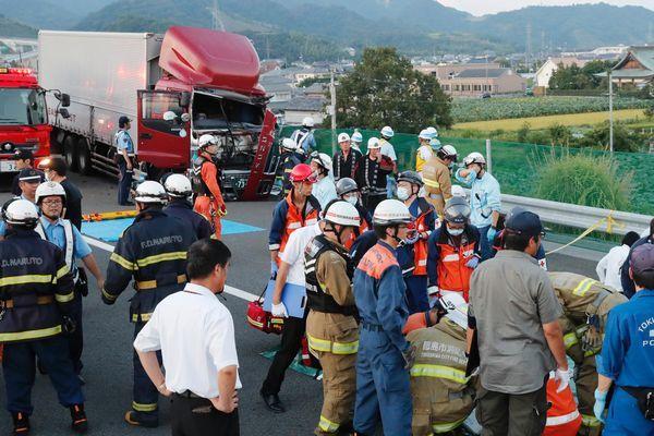 マイクロバスにトラックが追突し、2人が死亡した事故現場で負傷者の状況を確認する救急隊員ら=25日午後6時半、鳴門市大津町大幸の徳島自動車道