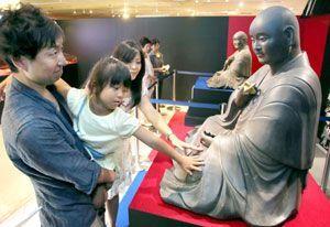 複製された弘法大師坐像に触れる親子連れ=そごう徳島店