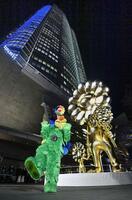 東京都港区の六本木ヒルズで公開された、アーティスト村上隆さん(左)の新作の彫刻「お花の親子」=26日午後