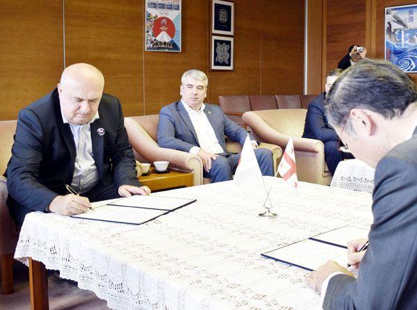 協定書にサインする飯泉知事(右)とスヴァニゼ会長(左)=県庁