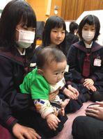 試験的に行われた「赤ちゃん先生」の授業で赤ちゃんを抱っこする児童=2月、藍住南小