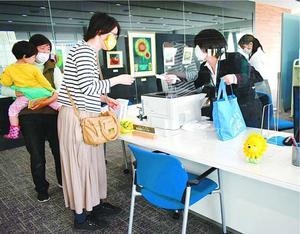 オープンした図書館カウンターで利用者に対応する職員(右)=阿南市役所