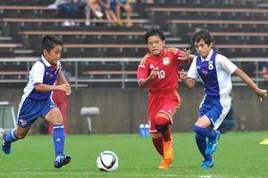 少年の部決勝・松茂対YMCA 前半、松茂の小林洸翔君(中)がドリブルで攻め込む=徳島市球技場