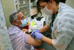 エルサレムの診療所で、3回目の新型コロナワクチン接種を受ける男性=1日(共同)