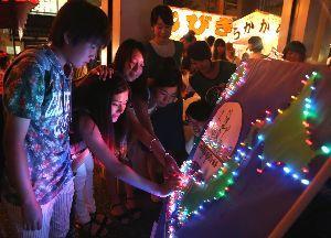 日本地図が張られたパネルにLEDを光らせる観光客=徳島市南内町2