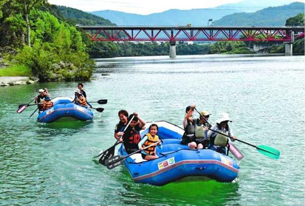 ボートに乗ってパドルをこぐ参加者=三好市池田町イタノの池田湖水際公園