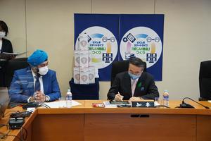 タブレット端末に署名する飯泉知事(右)=県庁